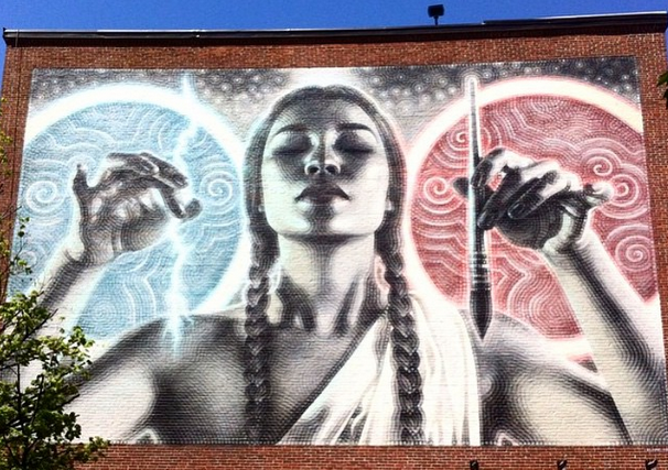 mural of a woman with braided hair holding a paintbrush